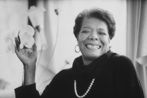 8th January 1993: Headshot portrait of African-American author Maya Angelou wearing black sweater with a pearl necklace, smiling and holding flowers in one hand. (Photo by Stephen Matteson Jr/New York Times Co./Getty Images) Click on the image to be taken to the websource.