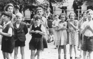 """A photograph of Jewish children in the Theresienstadt ghetto taken during an inspection by the International Red Cross. Prior to this visit, the ghetto was """"beautified"""" in order to deceive the visitors. Czechoslovakia, June 23, 1944. — Comite International de la Croix Rouge - Click on the link to be taken to the websource."""